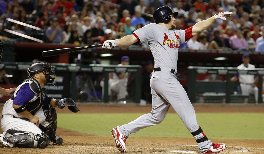 St. Louis Cardinals' Brandon Moss watches his two-run home run clear the fence as Arizona Diamondbacks' Welington Castillo, left, looks on during the fifth inning of a baseball game Wednesday, Aug. 27, 2015, in Phoenix. (AP Photo/Ross D. Franklin)