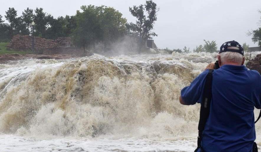 A torrent of water rushes through the typically mild waterfalls of Falls Park in Sioux Falls on Friday, Aug. 28, 2015, after flash floods hit the city over night. Some parts of the city got over 7 inches, more than twice the forecast rainfall. (AP Photo/Kevin Burbach)