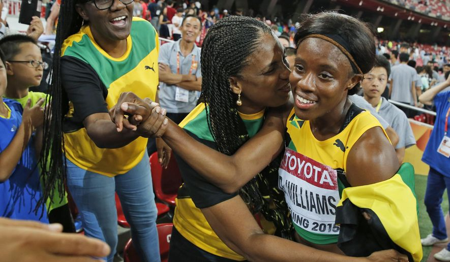 Jamaica's Danielle Williams celebrates with fans after winning the women's 100m hurdles final at the World Athletics Championships at the Bird's Nest stadium in Beijing, Friday, Aug. 28, 2015. (AP Photo/Ng Han Guan)
