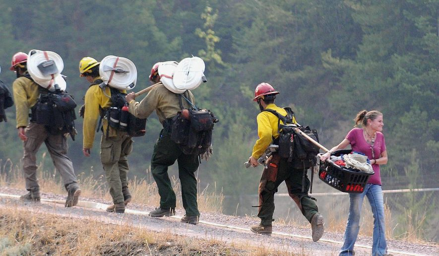 In this Thursday, Aug. 27, 2015 photo, Allison Stahl carries a basket of clothing to her car as firefighters walk past on their way to establish a hose line in Essex, Mont. The area was evacuated Thursday afternoon in the face of the growing Sheep Fire threatening the community at the southern edge of Glacier National Park. (Aaric Bryan/The Daily Inter Lake via AP)