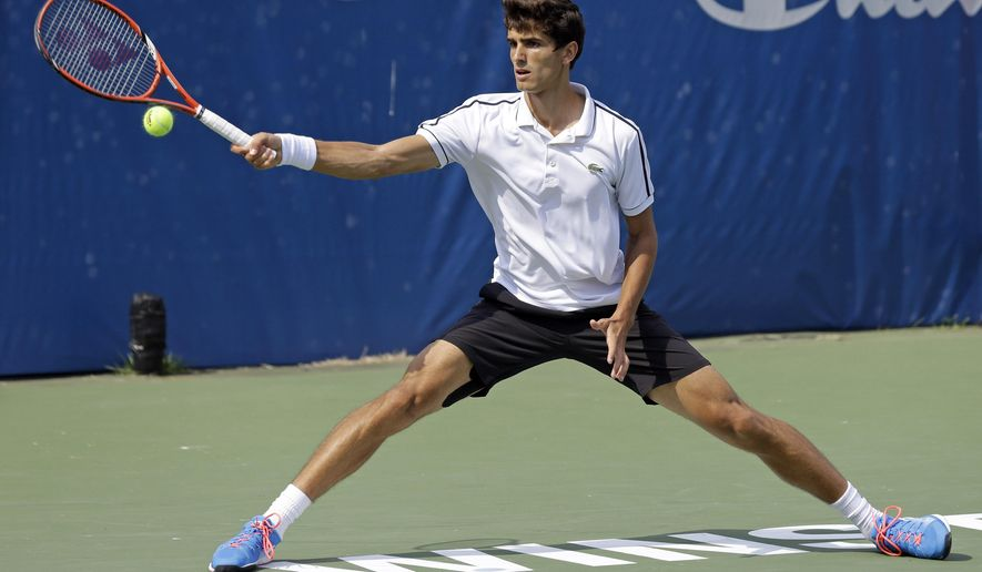 Pierre-Hugues Herbert, of France, reaches for the ball during a semifinal against Steve Johnson at the Winston-Salem Open tennis tournament in Winston-Salem, N.C., Friday, Aug. 28, 2015. (AP Photo/Gerry Broome)