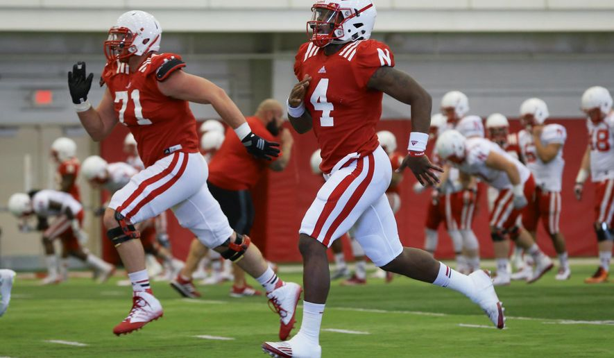 FILE - In this March 11, 2015, file photo, Nebraska quarterback Tommy Armstrong Jr. (4) and Nebraska offensive lineman Alex Lewis (71) run during spring practice in Lincoln, Neb., Wednesday, March 11, 2015. Fifteen months after he walked out of a Colorado jail, where he spent almost a month for his role in the 2013 beating of a man outside a bar, Lewis is one of the Cornhuskers' team captains, just like his dad Bill Lewis was in 1985. (AP Photo/Nati Harnik, file)
