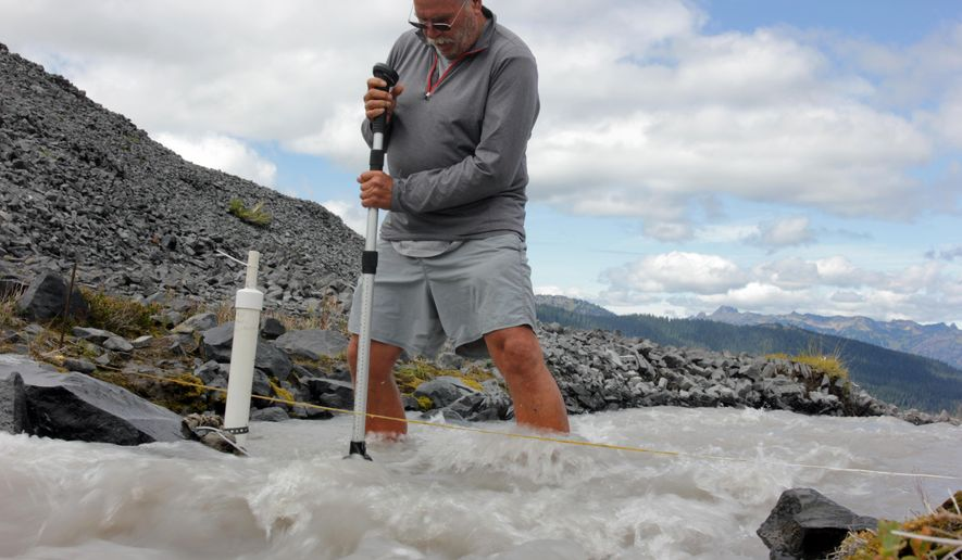 In this Aug. 7, 2015, photo scientist Oliver Grah measures the velocity of a stream of glacier melt stemming from Sholes Glacier in one of Mount Baker's slopes in Mount Baker, Wash. Glaciers on Mount Baker and other mountains in the North Cascades are thinning and retreating. (AP Photo/Manuel Valdes)