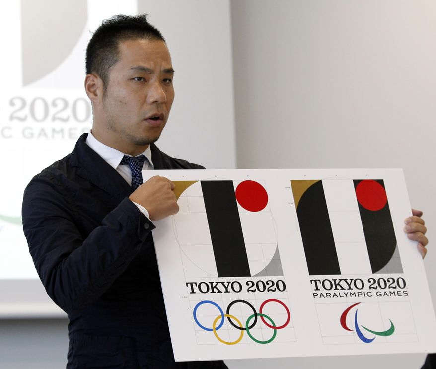 """FILE - In this Aug. 5, 2015, file photo, Japanese designer Kenjiro Sano gives a detailed explanation of how he came up with his logo, left, for the 2020 Tokyo Olympics at a press conference in Tokyo. Tokyo Olympic organizers defended Sano in a logo scandal Friday, Aug. 28, 2015, denying allegation his design for the 2020 Games was taken from a Belgian theater. The organizers disclosed Sano's initially submitted logo, saying its emphasis on """"T"""" shape had no resemblance to that of Theater de Liege and that a circle on the background was added later when his design was touched up. (AP Photo/Ken Aragaki, File)"""