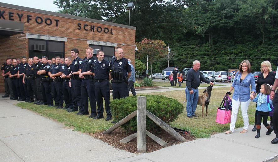 Akron Police officers and officers from area departments line the sidewalk wait to wish Charlee Winebrenner a good first day of school as she walks with her mother Alyse Shanafelt, left, and her grandparents Rob Winebrenner and Zee Shanafelt on her first day of school at Turkeyfoot School in Coventry Township, Ohio on Thursday, Aug. 27, 2015.  Charlee's father Akron Police officer Justin Winebrenner was shot in November 2014 while trying to get an unruly customer out of Papa Don's Pub in Akron. (Mike Cardew/Akron Beacon Journal via AP)  MANDATORY CREDIT