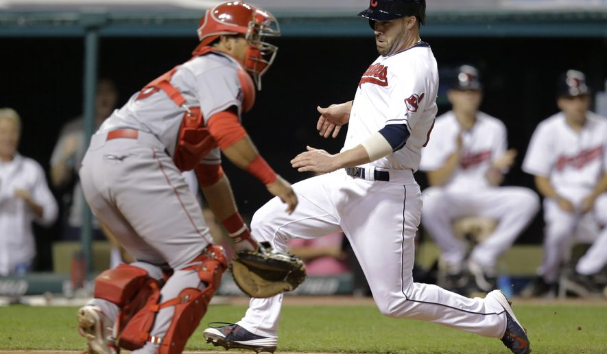 Cleveland Indians' Jason Kipnis, right, scores on a single by Carlos Santana during the seventh inning of a baseball game, Friday, Aug. 28, 2015, in Cleveland. Los Angeles Angels catcher Carlos Perez waits for the ball. The Indians won 3-1. (AP Photo/Tony Dejak)