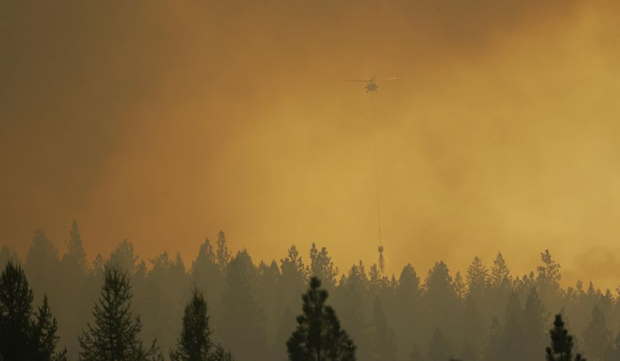 A helicopter makes a water bucket drop as it flies through smoky air while fighting a wildfire that flared up in the late afternoon near Omak, Wash., Thursday, Aug. 27, 2015. Firefighters were holding their own Thursday against the largest wildfire on record in Washington state, even as rising temperatures and increased winds stoked the flames. (AP Photo/Ted S. Warren)