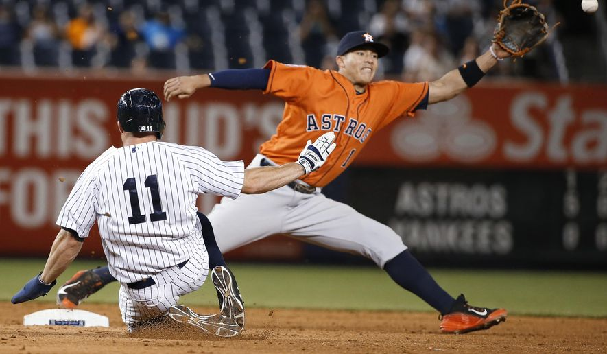 Houston Astros shortstop Carlos Correa (1)  keeps his foot on the bag as he reaches for a wide throw to put out New York Yankees' Brett Gardner on during the ninth inning of the Astros' 15-1 win over the Yankees in a baseball game at Yankee Stadium in New York, Tuesday, Aug. 25, 2015. Jacoby Ellsbury scored on the play, and Greg Bird was safe at first.. (AP Photo/Kathy Willens)