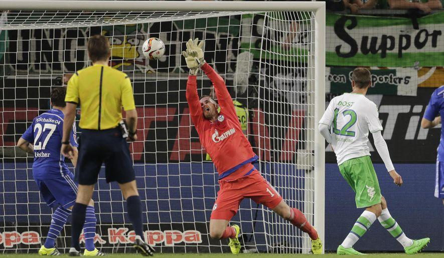 Wolfsburg's Bas Dost, right, scores his side's first goal during the German Bundesliga soccer match between Vfl Wolfsburg and FC Schalke 04 in Wolfsburg, Friday, Aug. 28, 2015. (AP Photo/Markus Schreiber).
