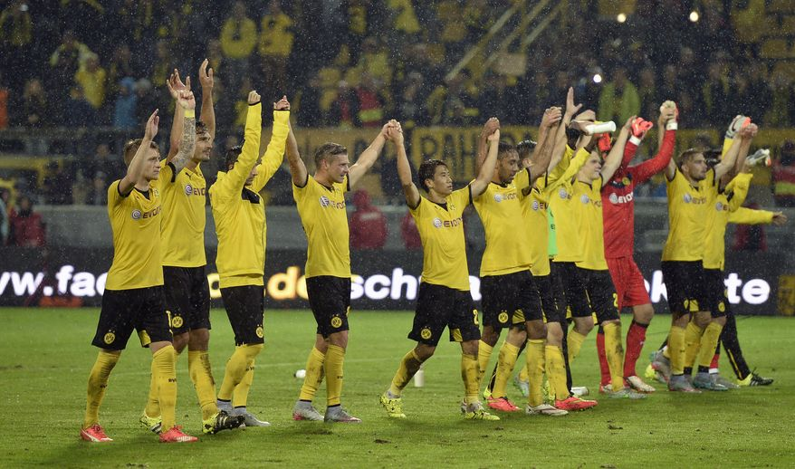 Dortmund's players celebrate after winning  the Europa League play-off 2nd leg soccer match between Borussia Dortmund and Odds BK in Dortmund, Germany, Thursday, Aug. 27, 2015. Borussia defeated Odds with 7-2.  (AP Photo/Martin Meissner)