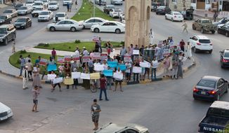 In this Thursday, Aug. 27, 2015, photo, local residents hold a demonstration against illegal immigration after hearing news that a boat carrying hundreds of migrants capsized off the coast, in Zuwara, Libya. (AP Photo/Mohamed Ben Khalifa)