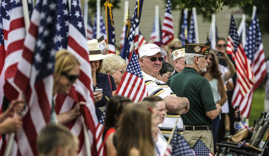 In this July 11, 2015 photo, people hold flags during a ceremony renaming Mayfair Park to Pfc. Andrew Meari Memorial Park in Joliet, Ill. Meari was killed on Nov. 1, 2010 while serving in Afghanistan. (Lathan Goumas/Herald-News via AP) CHICAGO TRIBUNE OUT MANDATORY CREDIT