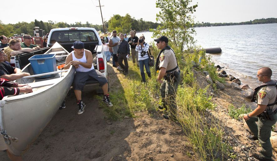 Conservation officer Tim Collette, center, approaches a group of Native Americans along the shore of Gull Lake, Friday, Aug. 28, 2015 in Nisswa, Minn. Conservation officers issued citations to two tribal members who attempted to net fish on Gull Lake in Nisswa on Friday, the second day of efforts by activists to assert rights they say they hold under an 1855 treaty. (Brian Peterson/Star Tribune via AP)  MANDATORY CREDIT; ST. PAUL PIONEER PRESS OUT; MAGS OUT; TWIN CITIES LOCAL TELEVISION OUT