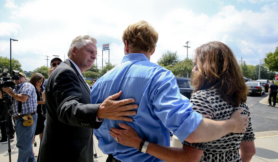 Virginia Gov. Terry McAuliffe, left, and his wife, Dorothy, right, visit with Chris Hurst, boyfriend of slain WDBJ-TV journalist Alison Parker, Friday, Aug. 28, 2015, in Roanoke, Va. Parker and fellow WDBJ-TV journalist Adam Ward were killed Wednesday by former colleague Vester Flanagan during a live broadcast. (Stephanie Klein-Davis/The Roanoke Times via AP)