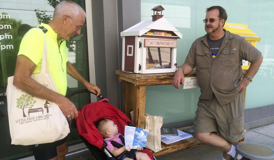 ADVANCE FOR WEEKEND EDITIONS AUG. 29-30 - In this Aug. 22, 2015 photo, Rick Brooks, left, and Todd Bol, right, built the second and first Little Free Libraries  as Brooks' 13-month-old granddaughter Josephine looks on during a celebration at the Central Branch of the Madison Public Library, in Madison, Wis. (Kate Stein/Wisconsin State Journal via AP) MANDATORY CREDIT