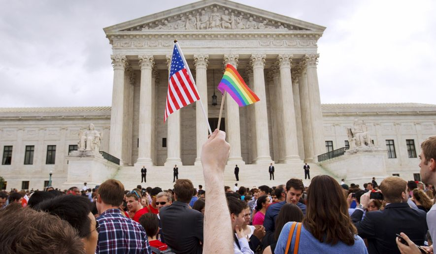 In this June 26, 2015, file photo, a man holds a U.S. and a rainbow flag outside the Supreme Court in Washington after the court legalized gay marriage nationwide. A federal appeals court ruled Friday that the Supreme Court can keep protesters off its marble plaza without violating their constitutional right to free speech. The U.S. Court of Appeals for the District of Columbia Circuit said that First Amendment rights stop at the sidewalk in front of the majestic courthouse and do not extend to the plaza. (AP Photo/Jacquelyn Martin)
