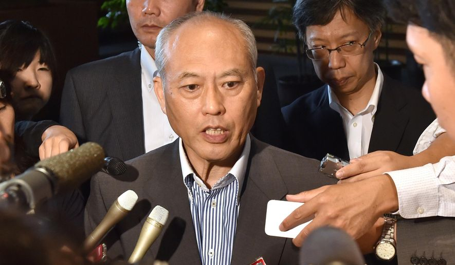 Tokyo Gob. Yoichi Masuzoe, center, speaks to reporters following a meeting of Cabinet ministers on a new national stadium construction plan for the 2020 Tokyo Olympics at prime minister's official residence in Tokyo Friday, Aug. 28, 2015. (Kazuhiro Nogi/Pool Photo via AP)