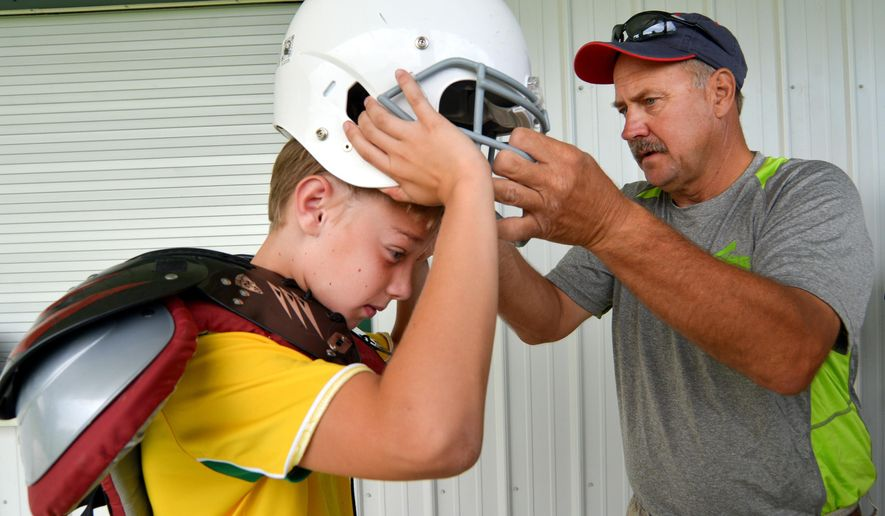 Chuck Walters, right, helps Robby Porter, 11, pull off a helmet that is too tight during the the Sheridan Recreation Department's little league football gear handout day on Aug. 15, 2015 in Sheridan, Wyo. Sheridan County coaches are part of a national movement to curtail concussions and make sports safer for athletes from the youngest children up to the professional ranks. (Justin Sheely /Sheridan Press via AP) ** FILE **