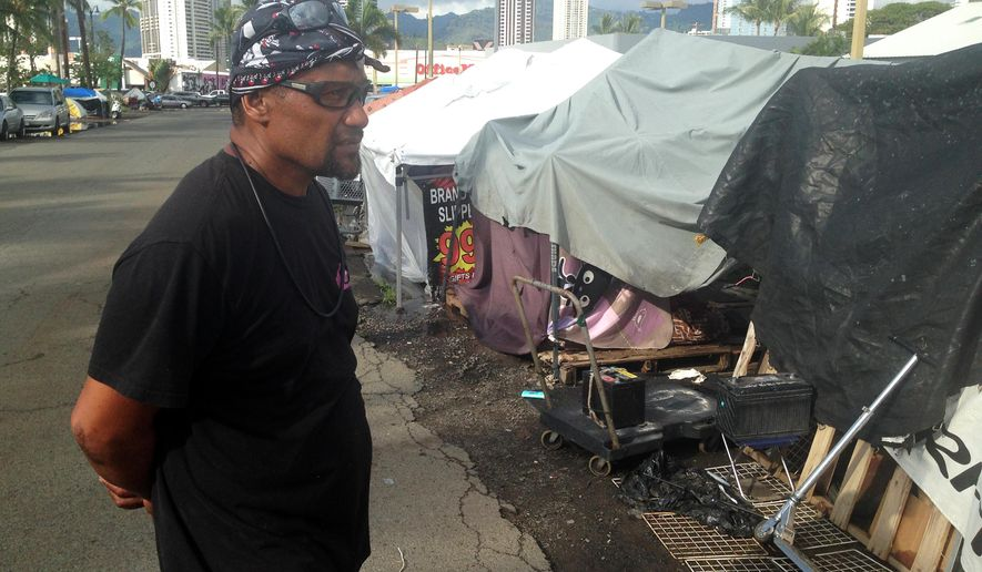 Vito Talo stands outside the structures he calls home on Ohe Street on Thursday, Aug. 27, 2015, in Honolulu. Talo's street is among those in a homeless encampment that are going to be cleared in a little more than a week. Honolulu Mayor Kirk Caldwell announced Thursday that enforcement of a rule that prohibits storing property on sidewalks will begin on the outer edges of the camp on Sept. 8. (AP Photo/Cathy Bussewitz)