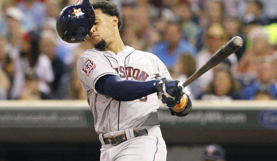 Houston Astros' Carlos Gomez loses his batting helmet as he swings for a strike against Minnesota Twins starting pitcher Kyle Gibson during the fourth inning of a baseball game in Minneapolis, Friday, Aug. 28, 2015. (AP Photo/Ann Heisenfelt)