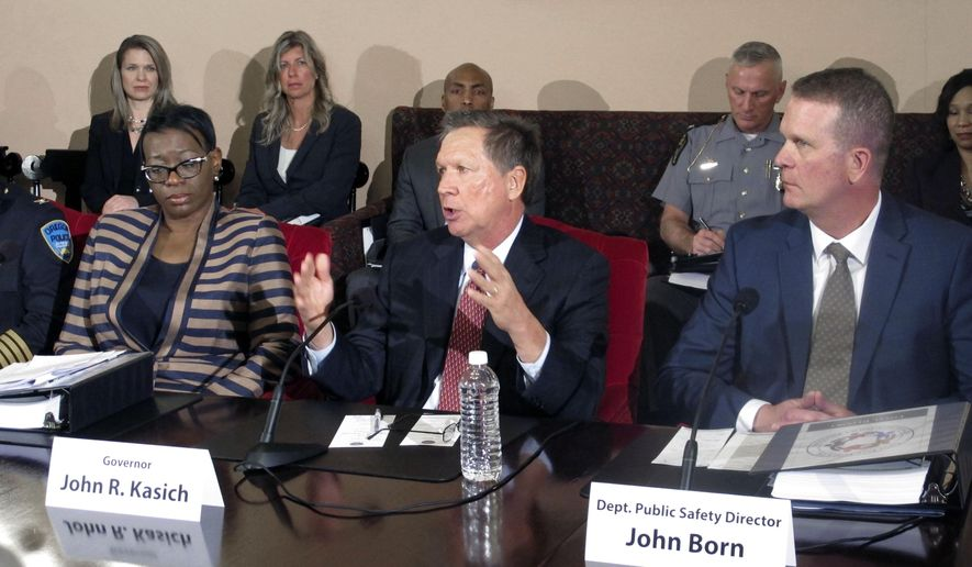 FILE - In this April 29, 2015, file photo, Ohio Gov. John Kasich, center, announces a plan in Columbus, Ohio, to establish the first-ever statewide police standards for the proper use of force, recruiting and hiring. Former state Sen. Nina Turner, left, and state Public Safety Director John Born, right, played roles in creating the standards adopted Friday, Aug. 28, 2015, and headed to hundreds of law enforcement agencies, limiting use of deadly force by police officers to defending themselves or others from serious injury or death. (AP Photo/Andrew Welsh-Huggins, File)