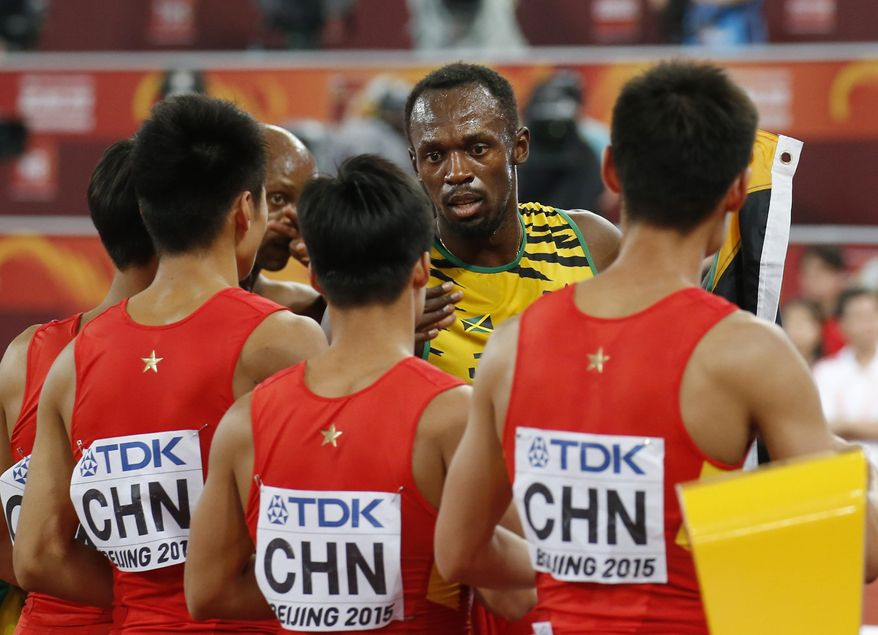 Jamaica's Usain Bolt talks with the China's 4x100 relay team at the World Athletics Championships at the Bird's Nest stadium in Beijing, Saturday, Aug. 29, 2015. (AP Photo/Ng Han Guan)