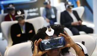 In this Jan. 6, 2015 file photo, Yasmin Moorman looks into the Galaxy Gear VR headset at the Samsung booth during the International CES, in Las Vegas. (AP Photo/John Locher, File)