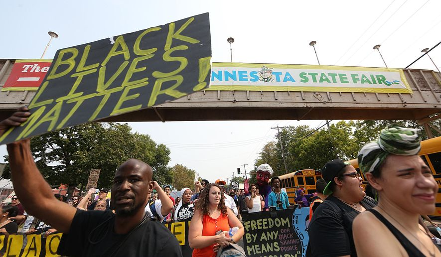 People march during a Black Lives Matter protest near the front gate of the Minnesota State Fair in Falcon Heights on Aug. 29, 2015. (Jim Gehrz/Star Tribune via Associated Press)