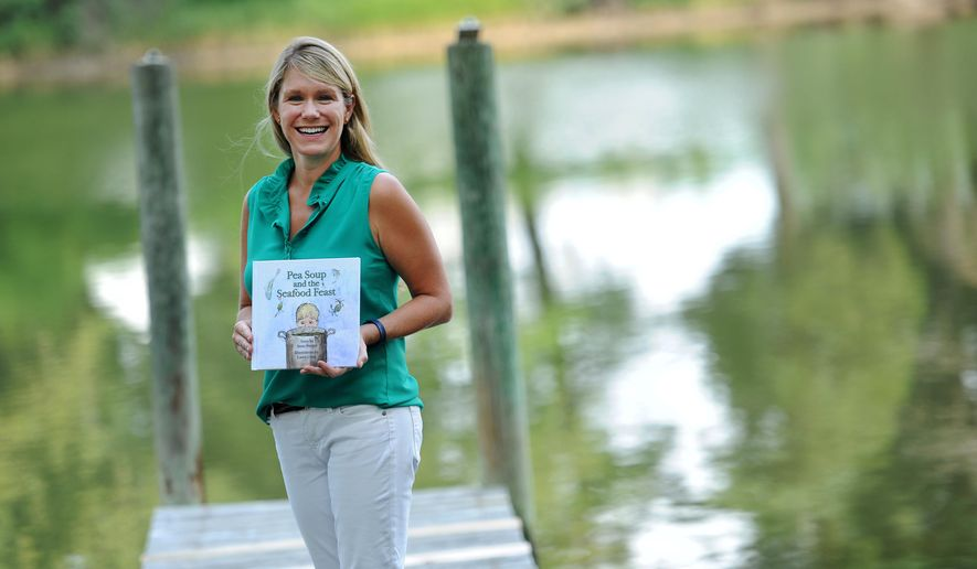 "Anna Burger holds her newly published children's book ""Pea Soup and the Seafood Feast"" at her home in Onancock, Virginia on Tuesday, Aug. 18, 2015. The book celebrates life on the water and the creatures of the Chesapeake Bay.  (Jay Diem /The Daily Times via AP)  NO SALES; MANDATORY CREDIT"