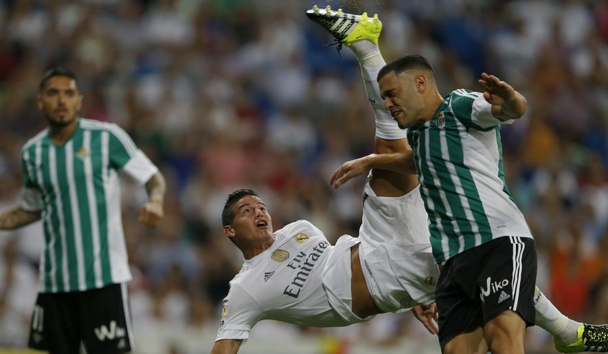 Real Madrid's James Rodriguez, centre, performs an overhead kick to score his side's fourth goal past Real Betis' Bruno Gonzalez, right, during a Spanish La Liga soccer match between Real Madrid and Real Betis at the Santiago Bernabeu stadium in Madrid, Saturday, Aug. 29, 2015. (AP Photo/Francisco Seco)