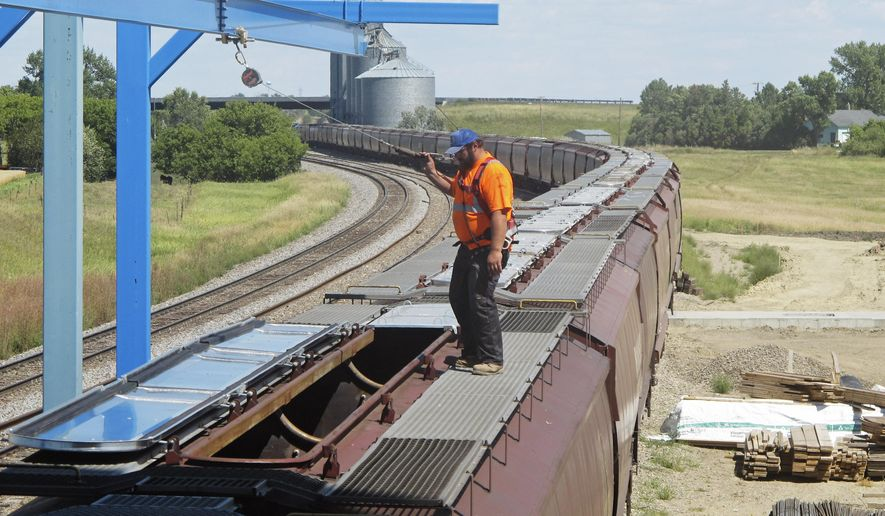 In this Aug. 20, 2015 photo, elevator worker Brian Grahn inspects a rail car about to be loaded with spring wheat in Sterling, N.D. With fall harvest fast approaching, farmers are expecting to get the trains they need to move crops to market, a turnaround from the past two years when elevators across North Dakota _ and in some other farm states _ were overflowing and mountains of grain were piled on the ground awaiting rail cars. (AP Photo/James MacPherson)