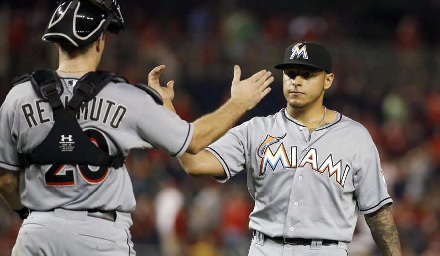 Miami Marlins catcher J.T. Realmuto (20) and relief pitcher A.J. Ramos celebrate after a baseball game against the Washington Nationals at Nationals Park, Friday, Aug. 28, 2015, in Washington. The Marlins won 4-3. (AP Photo/Alex Brandon)