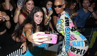 Amber Rose, right, takes a photo with a fan as she arrives at the MTV Video Music Awards at the Microsoft Theater on Sunday, Aug. 30, 2015, in Los Angeles. (Photo by Matt Sayles/Invision/AP)