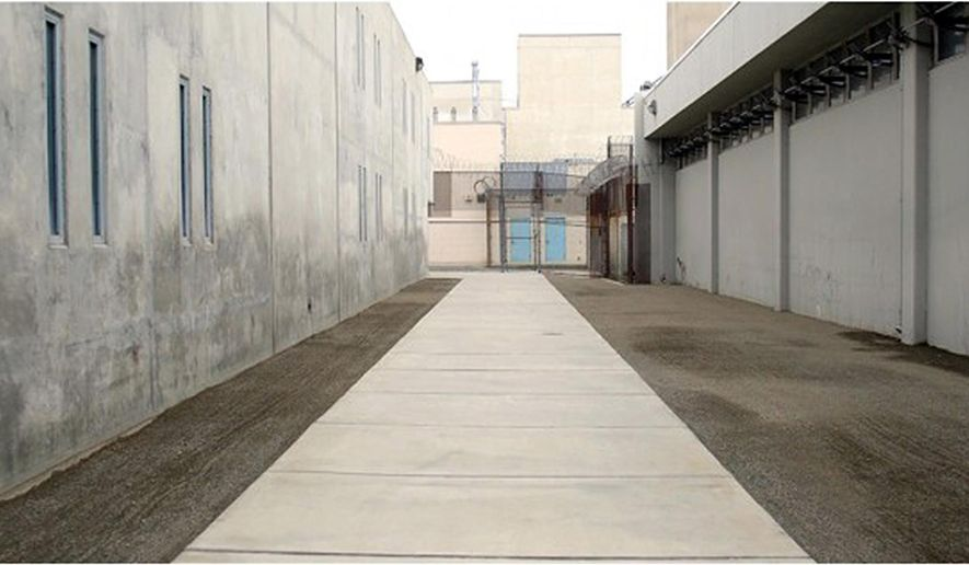 This recent but undated photo provided by the Orange County, Calif., Sheriff's Department shows a walkway flanked with gravel-covered areas that had previously been grass at the Theo Lacey jail in Orange, Calif. Inmates at Orange County's largest jail will get low-flow toilets and shower valves with timers as part of a wide-ranging effort to save water amid the state's four-year drought. The Orange County Register reported Saturday that the conservation plan at the jail also includes tearing up 3,000 square feet of grass and replacing it with decomposed granite.(Orange County Sheriff's Department via AP)