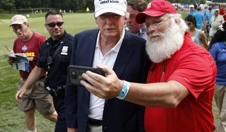 Republican presidential candidate Donald Trump, center, stops to take a photograph with Jim Tranz, of Port Charlotte, Fla., as he walks with a crowd during the final round of play at The Barclays golf tournament Sunday, Aug. 30, 2015, in Edison, N.J. (AP Photo/Mel Evans)