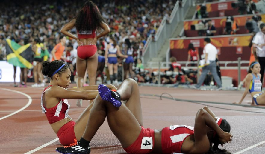 Allyson Felix of the United States, left, sits on the ground as the Jamaican team celebrate their gold medal in the women's 4x400m relay at the World Athletics Championships at the Bird's Nest stadium in Beijing, Sunday, Aug. 30, 2015.  (AP Photo/Andy Wong)