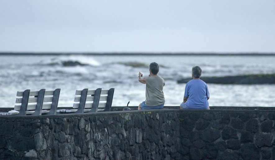 Jeri, left, and Jen Nakano, both from Hilo, sit near the ocean Monday, Aug. 31, 2015, in Hilo, Hawaii. Hurricane Ignacio rapidly weakened and moved farther away from the Hawaiian Islands, allowing forecasters to lift the tropical storm watches for the Big Island and Maui. (AP Photo/Caleb Jones) ** FILE **