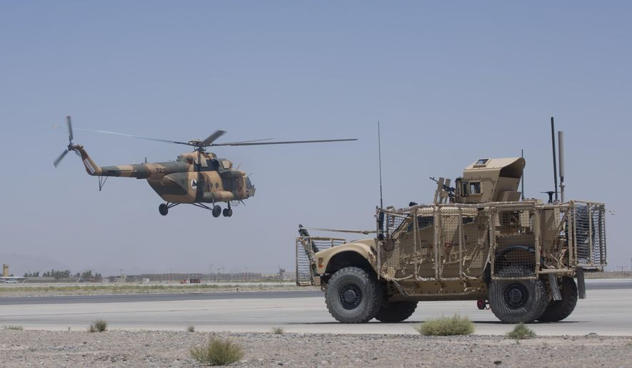 In this Tuesday, Aug. 18, 2015 photo, an Afghan National Army helicopter flies as a U.S. military vehicle passes, at Kandahar Air Base, Afghanistan. A series of airports, built by NATO to fight the Taliban, are being handed over to the Afghan government in a civil aviation upgrade that optimists hope will fuel not only regional trade but even tourism. The eight airfields, worth an estimated $2 billion, are scattered around a landlocked and mountainous land whose lack of rail transport or decent roads makes almost every intercity journey a perilous adventure -- even without factoring in attacks from Taliban militants. (AP Photo/Massoud Hossaini)