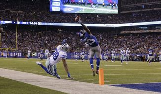 New York Giants wide receiver Odell Beckham (13) makes a one-handed catch for a touchdown against Dallas Cowboys cornerback Brandon Carr (39) in the second quarter of an NFL football game, Sunday, Nov. 23, 2014, in East Rutherford, N.J. (AP Photo/Julio Cortez)