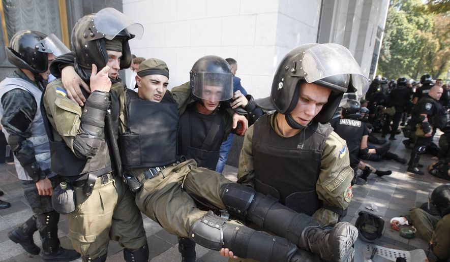Police officers give medical aid to a colleague after a grenade blast during a clash between protesters and police after vote to give greater powers to the east, outside the Parliament, Kiev, Ukraine, Monday, Aug. 31, 2015. (AP Photo/Vladimir Donsov)