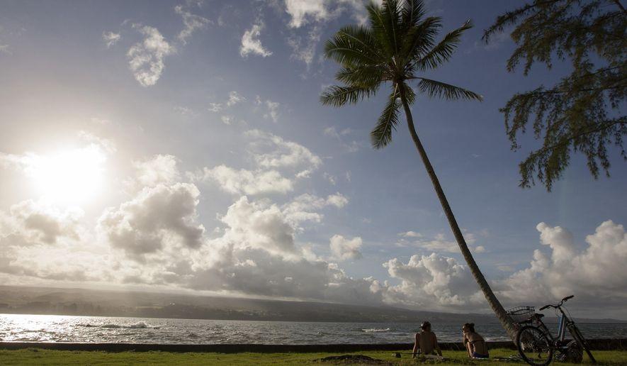 Keenin Ide, left, of Hilo, Hawaii, and Medea Yankova, of Sofia, Bulgaria, sit near Hilo Bay in Hilo Hawaii, Sunday Aug. 30, 2015. Hurricane Ignacio is forecast to weaken and move north of the Hawaiian Islands on Monday and Tuesday. (AP Photo/Caleb Jones)