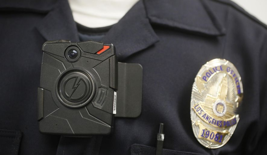 FILE- In this Jan. 15, 2014 file photo, a Los Angeles Police officer wears an on-body camera during a demonstration for media in Los Angeles. Some Los Angeles police officers are now equipped with the body cameras while on patrol. Police Commission President Steve Soboroff says Monday, Aug. 31, 2015 that the first wave of 860 cameras has been rolled out to more than 100 Mission Division officers who patrol the San Fernando Valley. (AP Photo/Damian Dovarganes, File)
