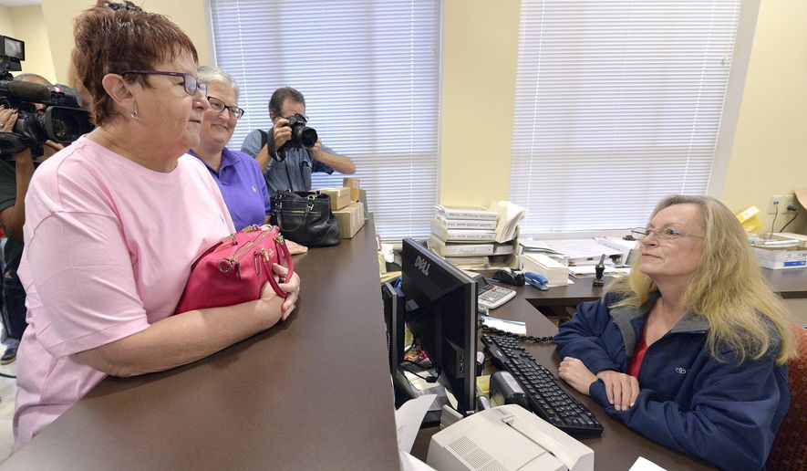 Karen Roberts, left, and her partner, April Miller, speak to Assistant Rowan County Clerk Kim Russell as they attempt to get a marriage license at the Rowan County Courthouse in Morehead, Ky., Tuesday, Sept. 1, 2015. Rowan County Clerk Kim Davis has refused to issue marriage licenses in defiance of a federal order. (AP Photo/Timothy D. Easley)