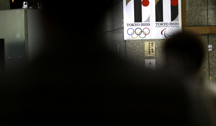 Visitors look at the logo of Tokyo Olympic Games 2020 at the Tokyo Metropolitan Government building in Tokyo Tuesday, Sept. 1, 2015.  Tokyo Olympic organizers on Tuesday decided to scrap the logo for the 2020 Games following another allegation its Japanese designer might have used copied materials. (AP Photo/Eugene Hoshiko)