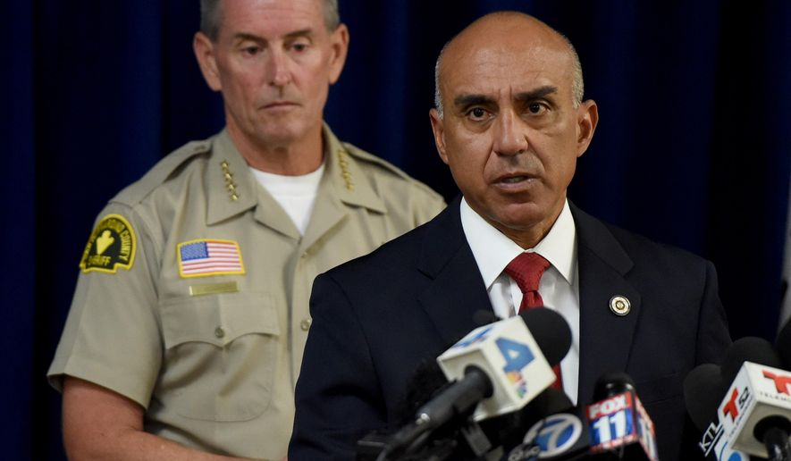San Bernardino County District Attorney Mike Ramos, joined by Sheriff John McMahon, speaks during a press conference, Tuesday, Sept. 1, 2015, in San Bernardino, Calif., announcing that felony assault charges have been filed against San Bernardino County Sheriff's Deputies Nicholas Downey, Michael Phelps, and Charles Foster in the in the televised beating of Francis Pusok. A KNBC-TV helicopter news crew followed the chase as Frances Jared Pusok fled deputies on a stolen horse. The station then televised deputies repeatedly punching and kicking Pusok as he lay on the ground. Seven other deputies placed on administrative leave following the April pursuit in the inland desert were not charged. (John Valenzuela/The Sun via AP) MANDATORY CREDIT