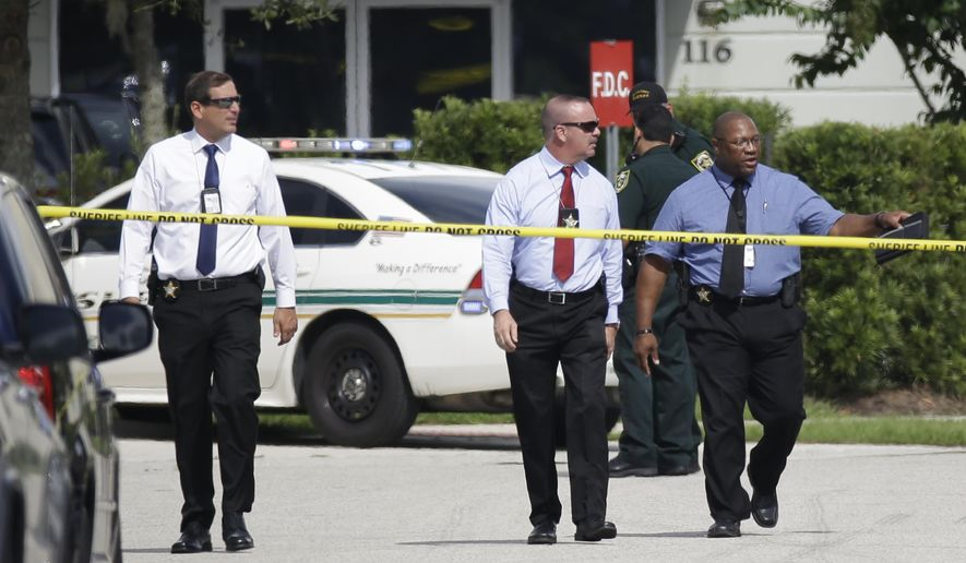 Law enforcement officials investigate the scene where an Orange County deputy shot a man who authorities say was stalking a female wrestler outside a World Wrestling Entertainment training facility, Monday, Aug. 31, 2015, in Orlando, Fla. The deputy had no choice but to shoot the man who he believed had a knife, Orange County Sheriff Jerry Deming said at a news conference. (AP Photo/John Raoux)