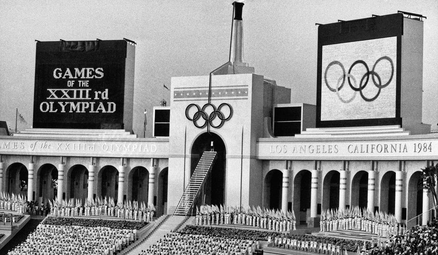 FILE - In this July 28, 1984 file photo, the Olympic flame is flanked by a scoreboard signifying the formal opening of the XXIII Olympiad after it was lit by Rafer Johnson during the opening ceremonies in the Los Angeles Memorial Coliseum. The U.S. Olympic Committee on Tuesday, Sept. 1, 2015, named Los Angeles as its candidate for the 2024 Games, replacing Boston's soured bid and marking a comeback for LA's dream of becoming a three-time host of the global sports competition. (AP Photo/Eric Risberg, File)