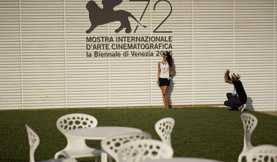 People take souvenir photos in front of the logo of the 72nd edition of the Venice Film Festival, at the Venice Lido, Monday, Aug. 31, 2015. The world's oldest movie festival will open on  Sept. 2 through Sept. 12. (AP Photo/Andrew Medichini)