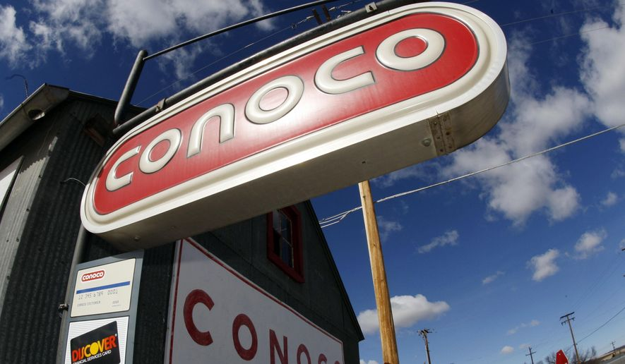 FILE - In this March 8, 2008 file photo, clouds hover over Conoco signs at a service station in Glenrock, Wyo. Energy company ConocoPhillips on Tuesday, Sept. 1, 2015 said it is cutting around 1,810 jobs, or 10 percent of its workforce, following a plunge that took oil prices to their lowest levels in years. (AP Photo/David Zalubowski, File)