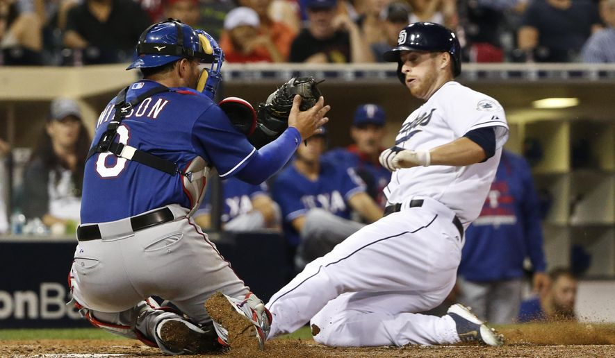 San Diego Padres' Cory Spangenberg slides into home as Texas Rangers catcher Bobby Wilson catches the throw in the sixth inning of a baseball game Monday, Aug. 31, 2015, in San Diego. Spangenberg was safe after Wilson failed to get the tag. (AP Photo/Lenny Ignelzi)